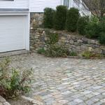 Aged cobblestone (Belgian Block) ramp with channel drain and fieldstone retaining walls