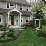 Formal plantings, stone wallk and arbor all add interest to the front entrance view