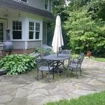 Broken bluestone patio creates an informal sitting area in the back yard