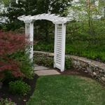 Fieldstone wall adds continuity between the stepping stone path and the lawn beyond.