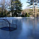 Combination ice skating rink and granite edged asphalt tennis and play court. Removable plugs allow for easy flooding and draining of the ice rink.