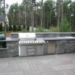 Custom Van Tassel Granite Outdoor Kitchen with honed lilac Bluestone Counter top.  Components include built-in Grill, sink, ice chest, cabinets and Big Green Egg.