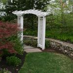 Lilac colored stepping stone path with Arbor and mixed fieldstone retaining wall